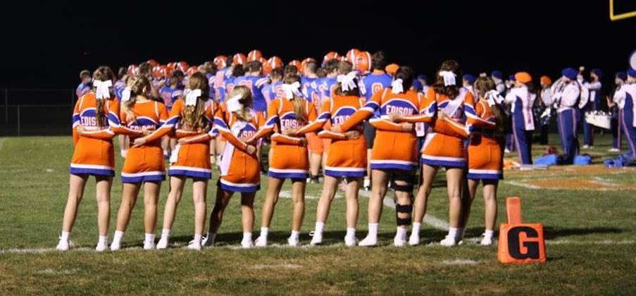 Cheerleaders sing the alma mater